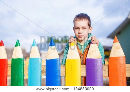 Boy behind the fence of colored pencils. copy space for your text