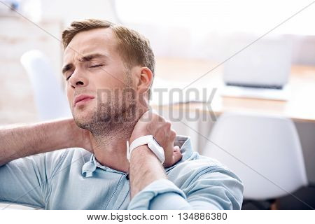 How resist pain. Moody sick man sitting on the couch and feeling ache while touching his neck