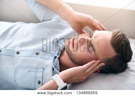 Severe disease. Cheerless sick man lying on the sofa and holding his hands on the temples while having a headache