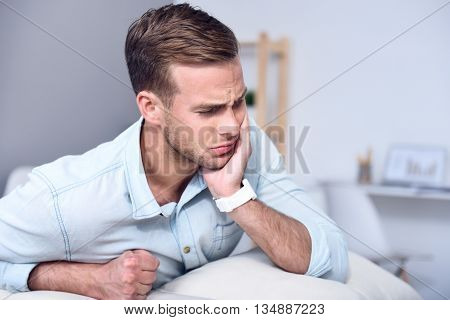 You should visit your doctor. Cheerless sick man sitting on the couch and feeling pain while holding hand on the face