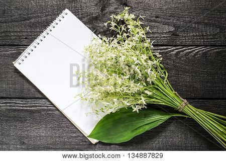Delicate bouquet of wild orchids also known as Lesser Butterfly Orchid (Platanthera bifolia) and notebook with space for text on a dark wooden table poster