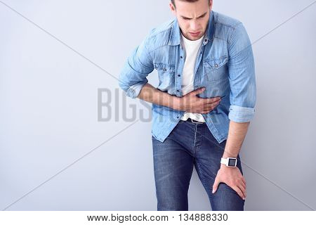poster of Harsh pain. Pleasant ill man holding his hand on the stomach and writhing under pain while standing isolated on white background