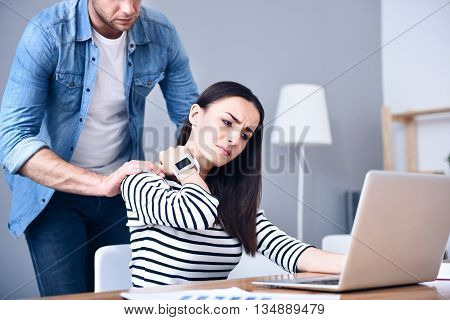 I need massage. Pleasant cheerless sick woman having an ache in neck and using laptop while the boyfriends holding hand on her shoulders