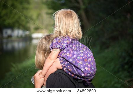Young Mother Giving Piggyback Ride To Her Daughter Outdoor