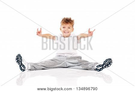 Happy little boy doing gymnastics. Studio portrait isolated over white background.