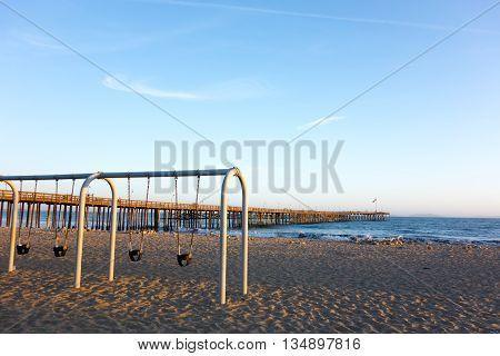 Empty kids swings at golden hour at Ventura sandy city beach near famous historic wooden pier Ventura California