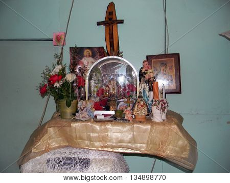 CEBU CITY, CEBU / PHILIPPINES - JULY 30, 2011: Roman Catholic images decorate an altar attached to a wall in a home in the Philippines.