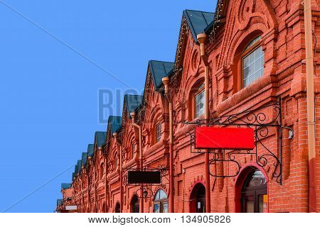 Vintage shopping arcade - architecture background. Exterior architecture of old shopping arcades of the 19th century. Russian stone architecture of the 19th century. Old brick building.