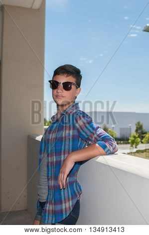 Teenage girl with crew cut resting against concrete rail.