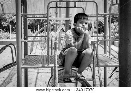 asian boy sitting alone at playground black and white tone