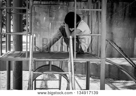 Girl pauper sitting alone at playgroundblack and white tone