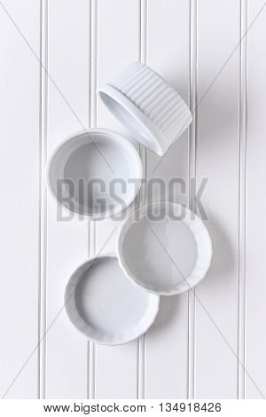 White on white still life of a group of ramekins arranged on a table. The bowls are empty in vertical format.