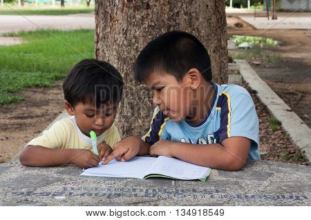 Little boy use pen writting on notebook in the park