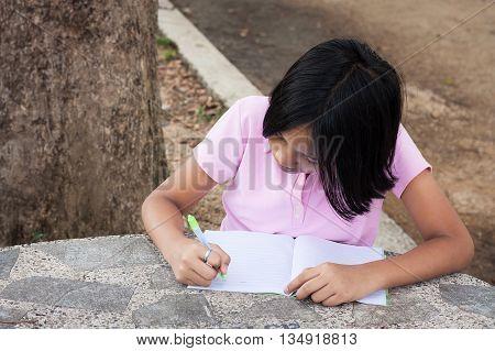 cute girl writing book in the garden