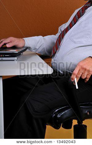 Business man at desk holding a cigarette