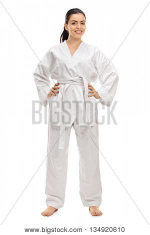 Full length portrait of a young female martial artist in a white kimono isolated on white background