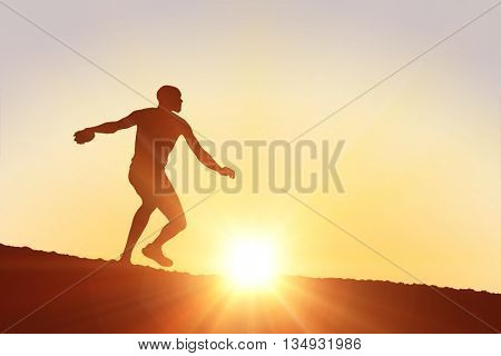 Athlete man throwing a discus against clouds