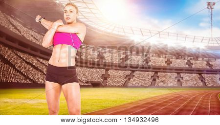 Female athlete stretching and listening music against view of a stadium