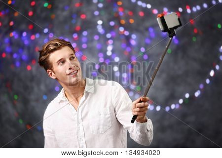Young handsome man taking selfie on blurred colourful lights background