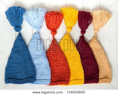 colorful baby knitted hats folded in row on white painted table, top view