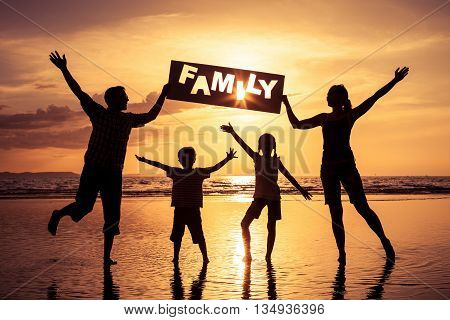 Silhouette of happy family who standing on the beach at the sunset time. Family having fun on the sea. Concept of friendly family and of summer vacation.
