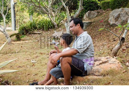 father playing bubble soap with his son in the park