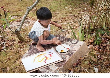 little playing panit on white paper in the park