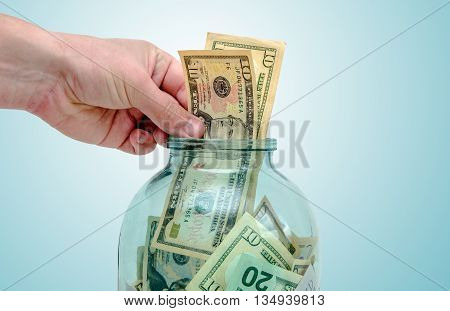 man's hand puts the US currency in a jar of glass