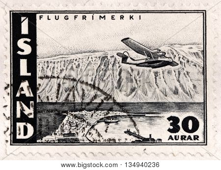 LUGA RUSSIA - APRIL 12 2016: A stamp printed by ICELAND shows Flying Boat over Skutulsfjordur - a big fjord in the north side of the Westfjords. It surrounds the town of Isafjordur circa 1947