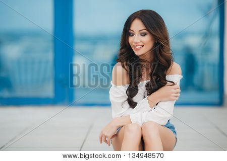 Young beautiful brunette woman with long curly hair and gray-green eyes, dressed in a white shirt and blue denim shorts, posing in the city alone, sitting in the open air in the summer on a background of show-windows with blue glass