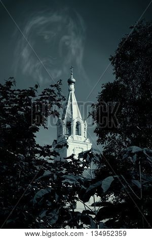 Watch tower of Spaso-Prilutsky Monastery in the Vologda city Russia. Bell tower. Monochrome gamma. Jesus Christ face in the sky