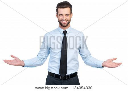 You are always welcome! Confident young handsome man in shirt and tie stretching out hands and smiling while standing against white background