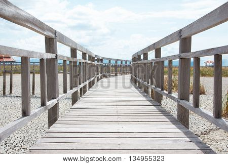 closeup perspective wooden bridge with dry earth and cracked ground
