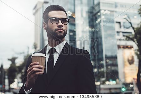 Rebooting after hard working day. Confident young man in formalwear holding coffee cup and looking away while standing outdoors with cityscape in the background