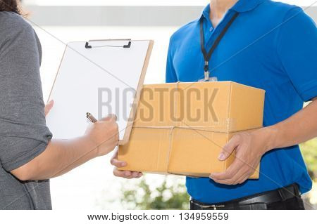 Woman hand signing receipt of delivered package. Delivery concept. Receiving package