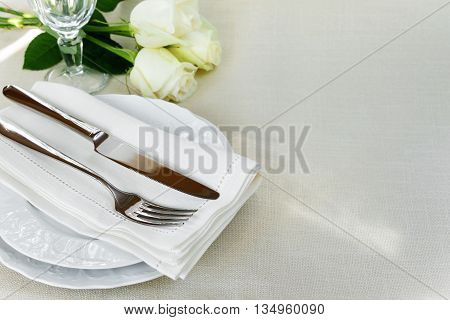 Beautiful decorated table with white plates crystal glass linen napkin cutlery and white rose flower on tablecloths with space for text