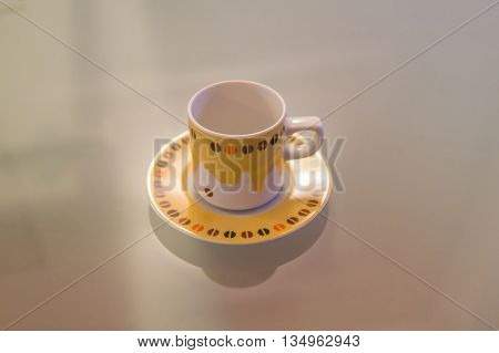 Yellow and white coffee cup decorated over a modern table