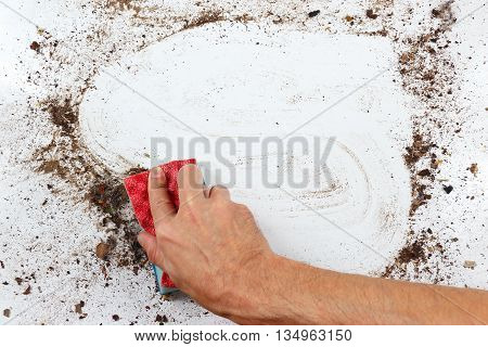 Hand with sponge cleans a heavily dirty surface