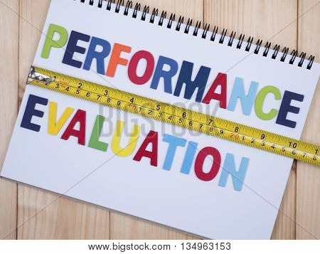 Word spelling Performance Evaluation and measuring tape on white notebook with wood background