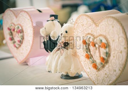Close focus on bride bear doll beside with groom bear doll and pink paper boxes in heart shape which decorated for wedding night.