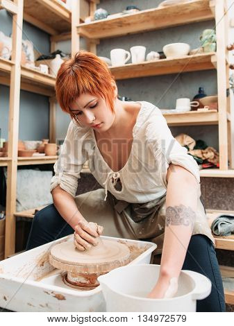 Young female potter working with clay at studio. Front view on red woman potter making pottery on potters wheel. Pretty female potter takes some clay from bucket for work