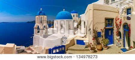 Picturesque view of white houses and church with blue domes in Oia or Ia, island Santorini, Greece