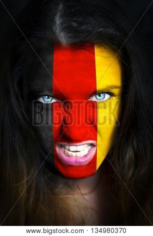 Portrait of a woman with the flag of the Germany painted on her face.