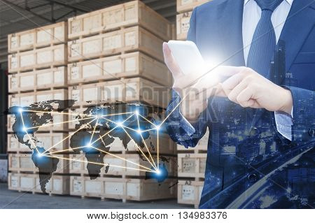 Double exposure of businessman using smart phone network connection world map by NASA city of business center and blurred cargo warehouse background international transportation trading business concept