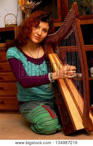 Girl Harpist In Ethno Outfit Playing Her Instrument.