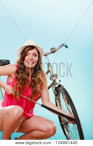 Happy young woman pumping up tire tyre with bike bicycle pump. Summer recreation activity.