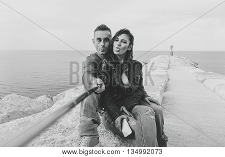 Funny tourist couple making selfie with self stick - Young people enjoying new trends for sharing on social network - Technology addiction concept - Black and white editing - Soft focus on face