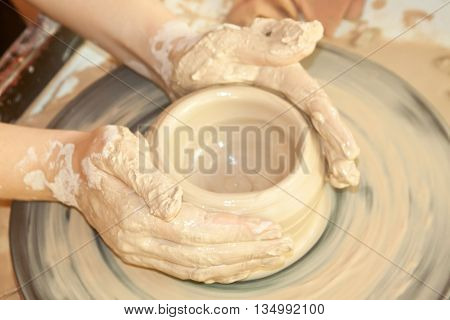 Female hands working on the pottery wheel