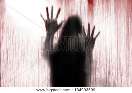 Horror woman behind the matte glass blood stain. Blurry hand and body figure abstraction.