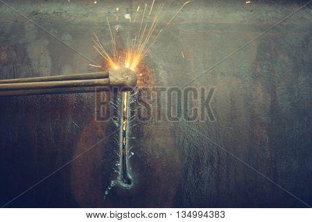 Metal cutting with acetylene torch.Staraya rusty pipe.